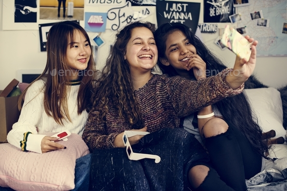Teenage girls using a smartphone to take a selfie in a bedroom hangout and friendship concept - Stock Photo - Images