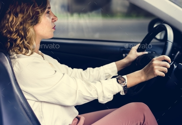 Woman driving a car on a road - Stock Photo - Images