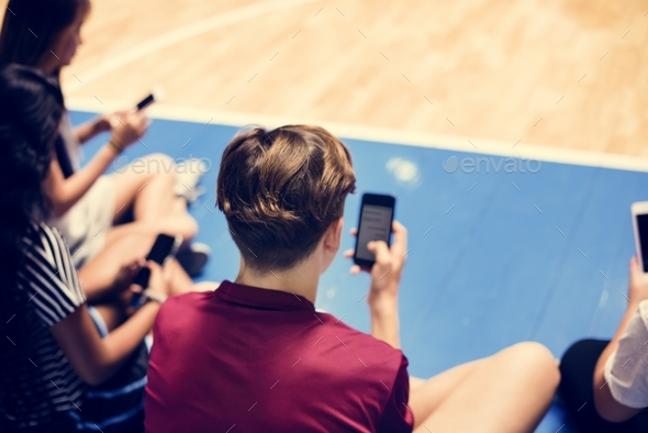 Group of young teenager friends on a basketball court relaxing and using smartphone - Stock Photo - Images