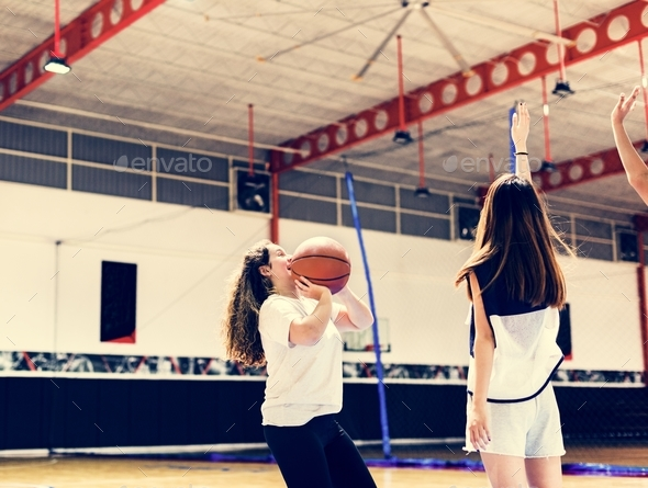 Teenage girl playing a basketball making a pass - Stock Photo - Images