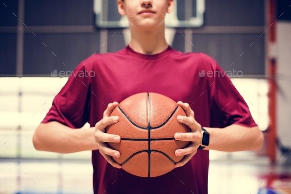 Teenage boy holding a basketball on the court - Stock Photo - Images