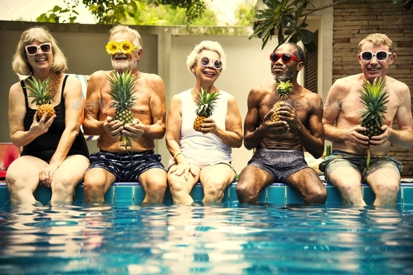 Group of diverse senior adults sitting at poolside holding pinea - Stock Photo - Images