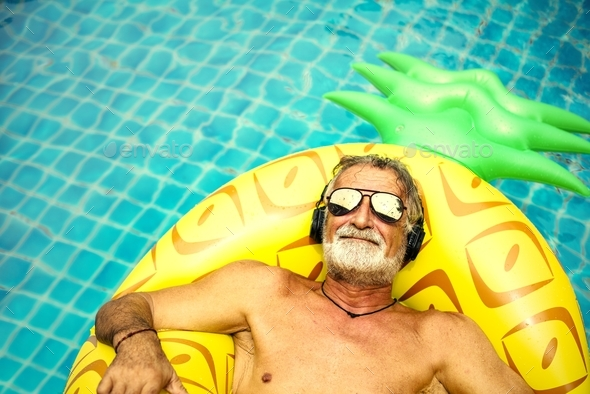 Closeup of caucasian senior man in the pool with headphones - Stock Photo - Images