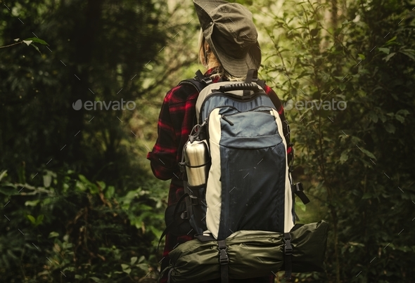 Woman trekking in a forest - Stock Photo - Images