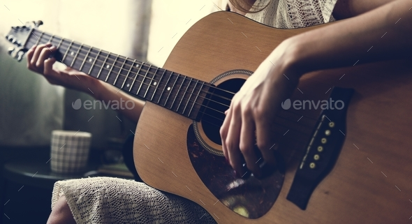 Caucasian woman relaxing and playing guitar - Stock Photo - Images