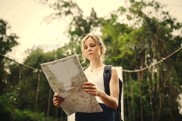 Woman following a map in nature - Stock Photo - Images