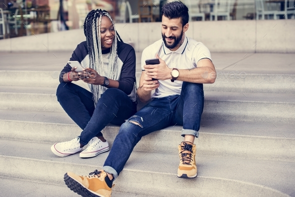 People sitting using smartphone together - Stock Photo - Images