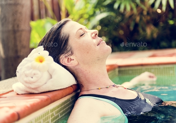 Woman enjoying the water in a swimming pool - Stock Photo - Images