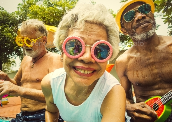 Closeup of diverse senior adults sitting by the pool enjoying su - Stock Photo - Images