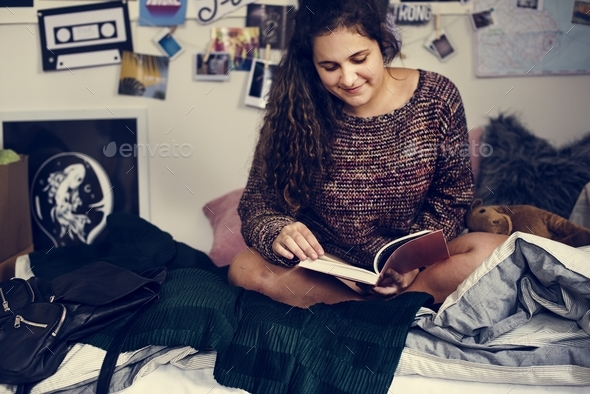 Teenage girl reading a book in a bedroom - Stock Photo - Images
