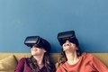 Two caucasian woman using VR on a sofa - PhotoDune Item for Sale