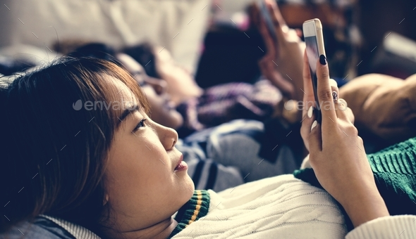 Teenage girls using smartphones on a bed internet in slumber party - Stock Photo - Images