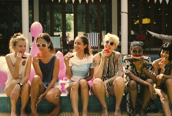 Group of girls friends eating watermelon at the pool - Stock Photo - Images
