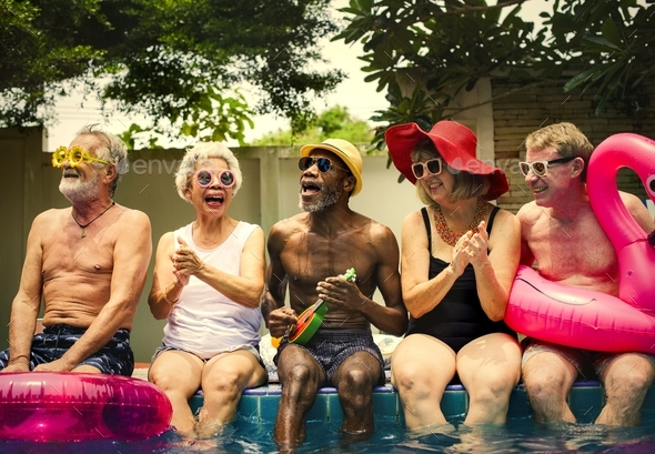 Group of diverse senior adults sitting by the pool enjoying summ - Stock Photo - Images