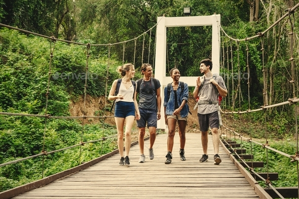 Friends walking on a bridge in nature - Stock Photo - Images