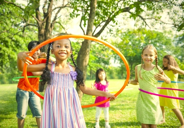 Cute diverse kids playing with hula hoops - Stock Photo - Images
