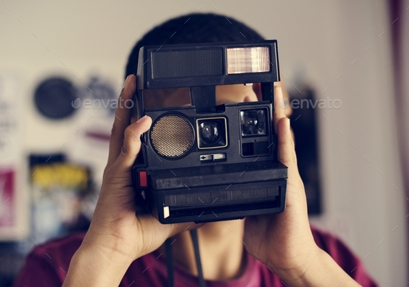 Teenage boy taking a picture in a bedroom hobby and photography concept - Stock Photo - Images