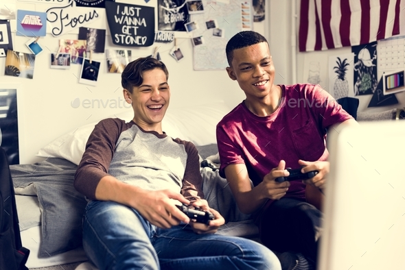 Teenage boys hanging out in a bedroom playing video games together - Stock Photo - Images