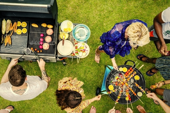 Group of diverse friends grilling barbecue outdoors - Stock Photo - Images