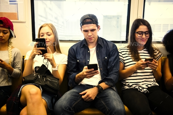 Group of young adult friends using smartphones in the subway - Stock Photo - Images