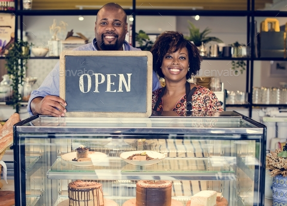 Cake cafe owners with open sign - Stock Photo - Images
