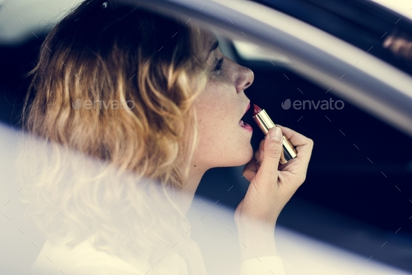 Woman putting on lipstick in a car - Stock Photo - Images