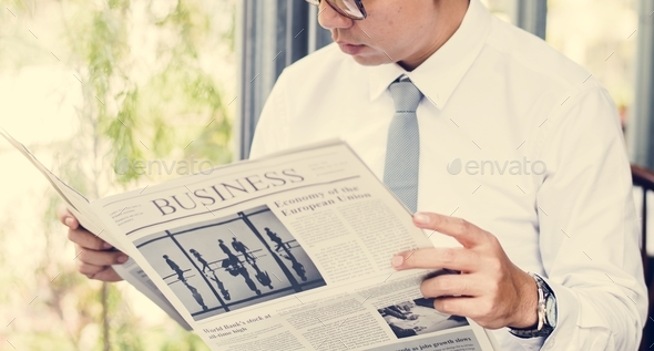 Businessman reading newspaper in the morning - Stock Photo - Images