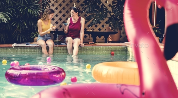 Girls relaxing by the swimming pool - Stock Photo - Images