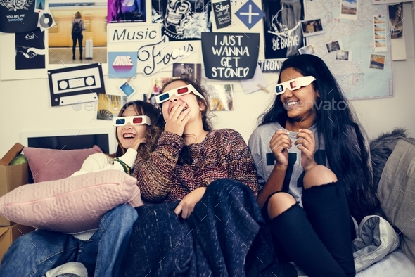 Teenage girls wearing 3d movie eyeglasses enjoying laughing and watching TV - Stock Photo - Images