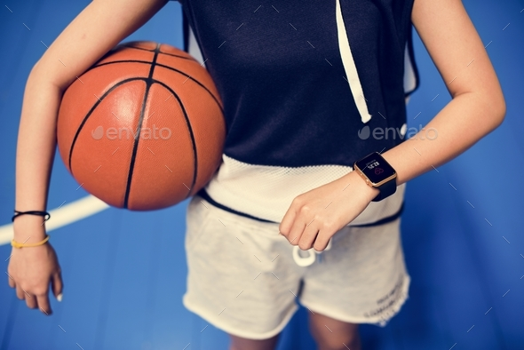 Teenage girl holding a basketball on the court - Stock Photo - Images