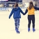Girl friends ice skating on the ice rink together - PhotoDune Item for Sale