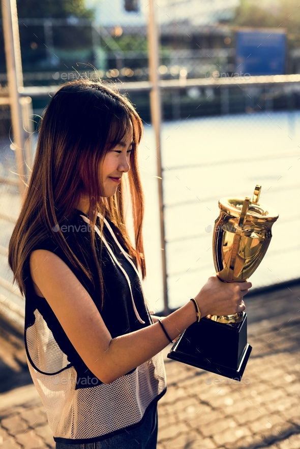 Asian teenage girl in sporty clothes holding a trophy outdoors - Stock Photo - Images