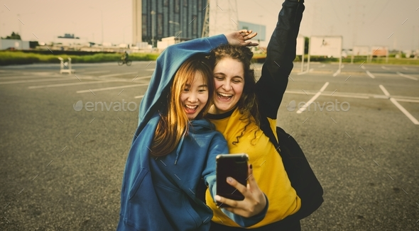 Girl friends smiling and taking a selfie together - Stock Photo - Images