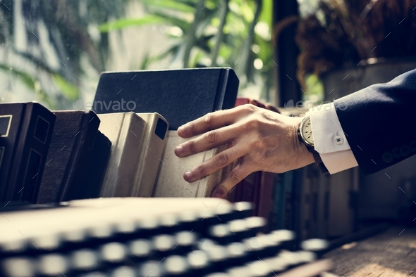 Closeup of hand getting a book - Stock Photo - Images