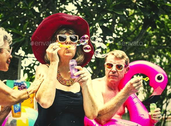 Group of diverse senior adults sitting at poolside blowing soap - Stock Photo - Images