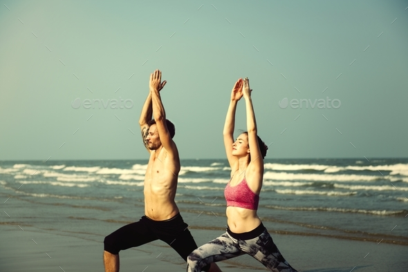 The couple is doing a yoga at the beach - Stock Photo - Images