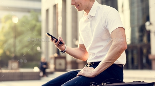 Young adult man checking his smartphone - Stock Photo - Images