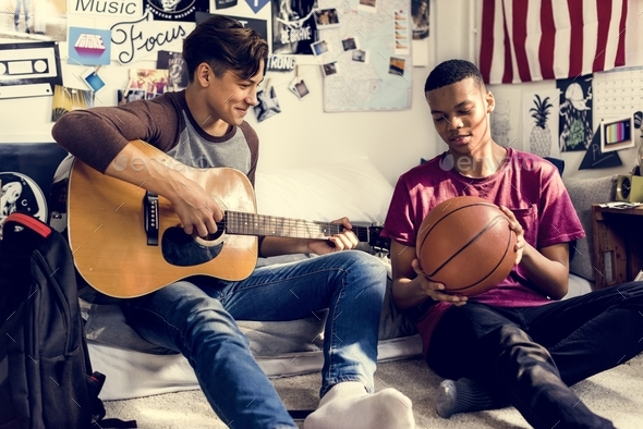 Teenage boys hanging out in a bedroom music and sports hobby concept - Stock Photo - Images