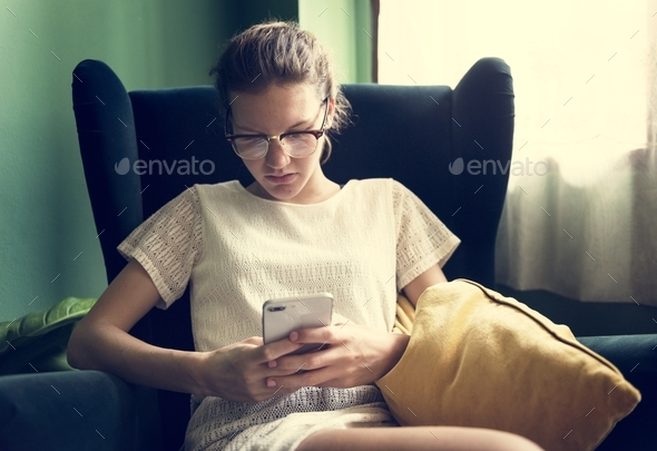 Caucasian woman using phone in living room - Stock Photo - Images