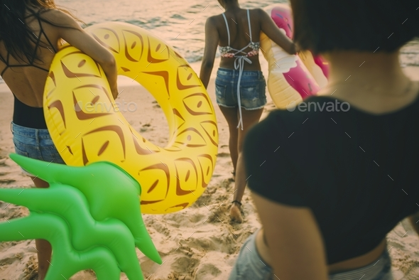 Group of diverse women walking at the beach with inflatable tube - Stock Photo - Images