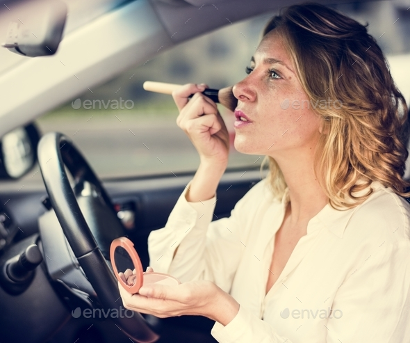 Woman wearing makeup in a car - Stock Photo - Images