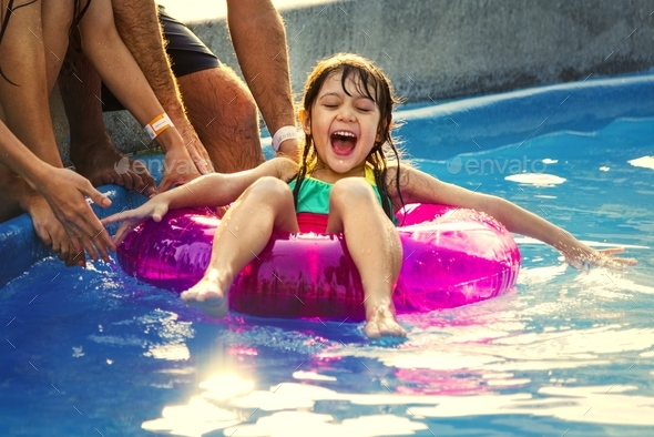 Little girl enjoying the pool on a summer float - Stock Photo - Images
