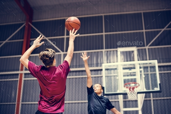 Two teenage boys playing basketball together on the court - Stock Photo - Images