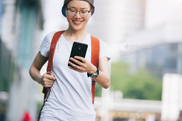 Asian woman use mobile phone on city street - Stock Photo - Images