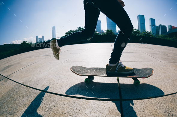 Skateboarder legs skateboarding at sunrise city - Stock Photo - Images