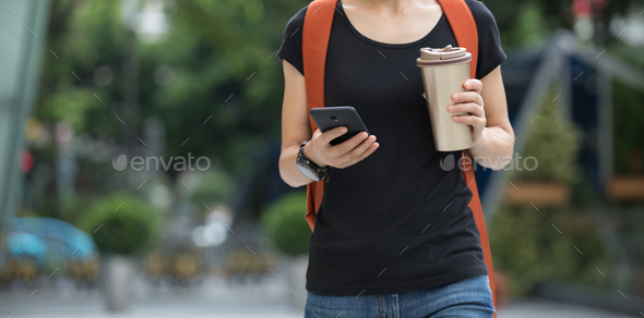 Walking with cup of coffee in hand - Stock Photo - Images