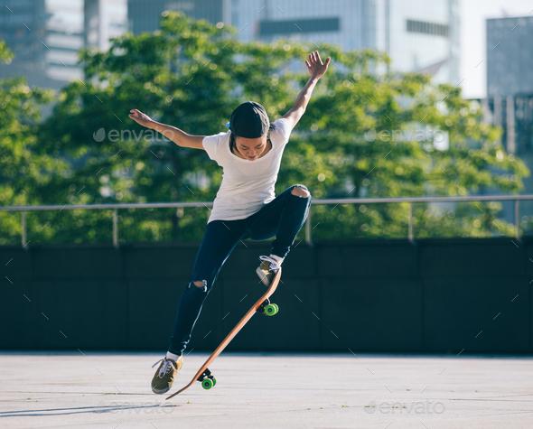 Skateboarder skateboarding at city - Stock Photo - Images