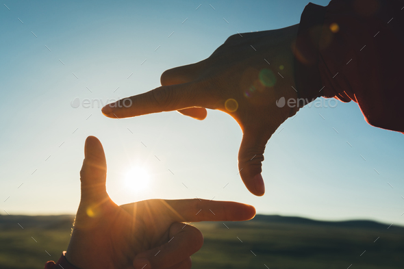 Hands making a frame against sunset - Stock Photo - Images