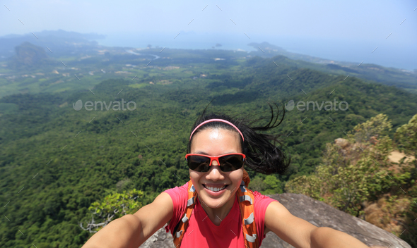 Taking selfie on cliff edge - Stock Photo - Images