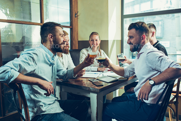 Team job while relaxing in pub. - Stock Photo - Images